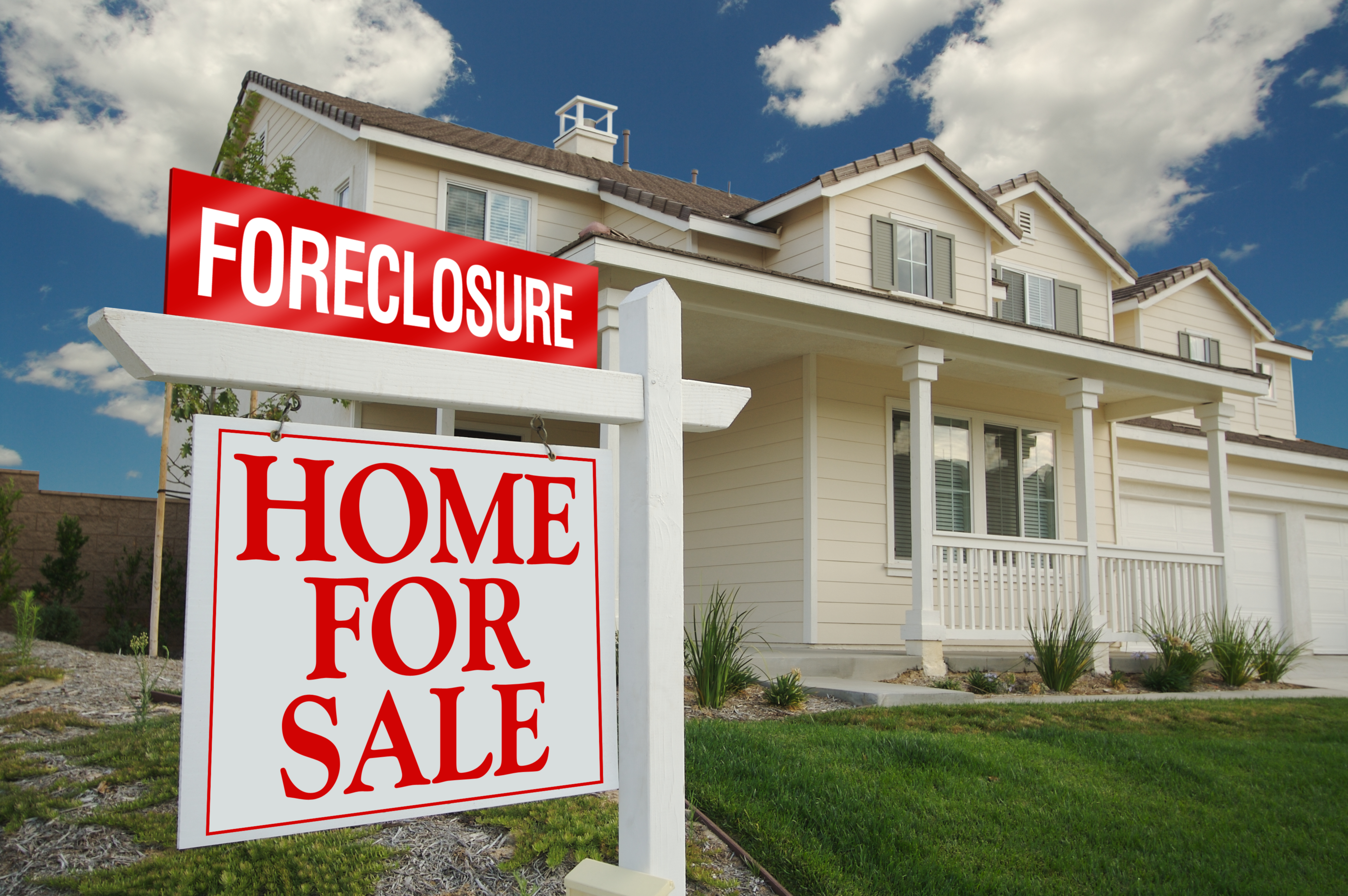 Foreclosure Sign and House with dramatic sky background.